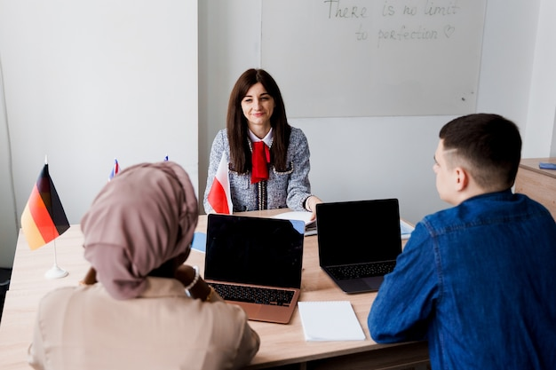 Wieloetniczni uczniowie i nauczyciel uczą się razem języków obcych w klasie.