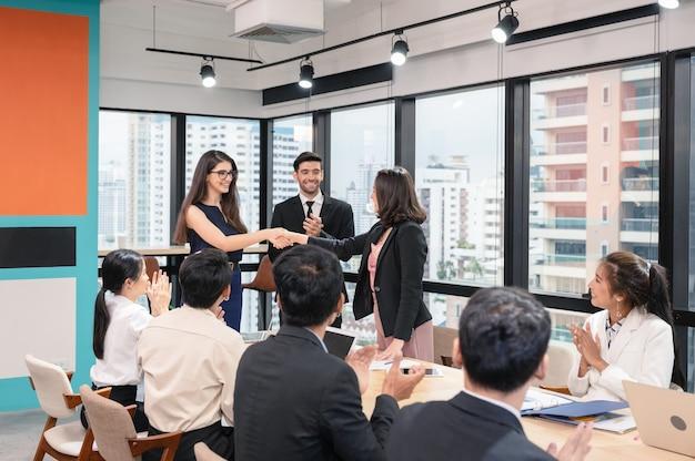 Wieloetniczny bizneswoman uścisk dłoni współpracy w zakresie porozumienia korporacyjnego ze współpracownikami w nowoczesnym biurze