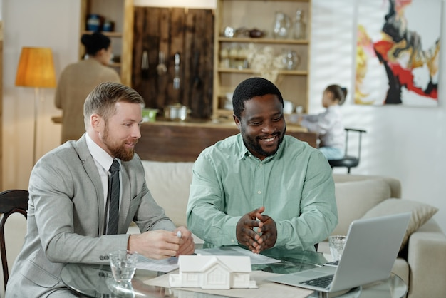 Wieloetniczny doradca finansowy i klient gromadzący się przy stole, oglądając laptopa podczas dyskusji