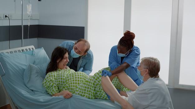 Wieloetniczny lekarz i pielęgniarka pomagający przy porodzie