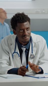 Wieloetniczny lekarz i stary pacjent robiący kontrolę z zielonym ekranem