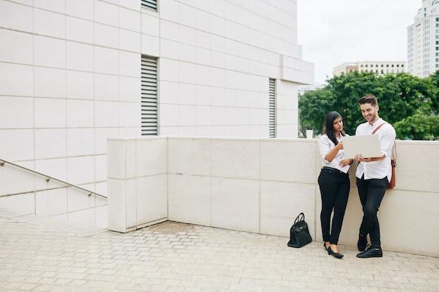 Wieloetniczny młody zespół biznesowy stojący na zewnątrz z laptopem omawiający ostatni raport lub prezentację produktu