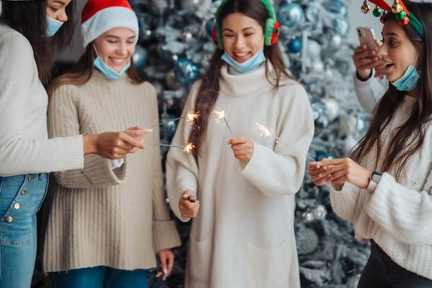 Wieloetniczny młodzi ludzie świętują sylwestra trzymając zimne ognie