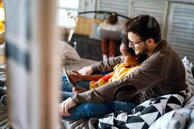 Wieloetniczny ojciec i dziecko za pomocą elektronicznego tabletu w domu. technologia, edukacja, koncepcja ludzi