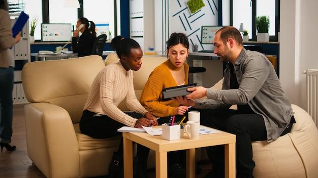 Wieloetniczny zespół analizujący informacje z tabletu omawiający siedzenie na kanapie podczas burzy mózgów nad nowym projektem dla start-upu. różnorodni biznesmeni analizujący sprawozdania finansowe podczas spotkania.