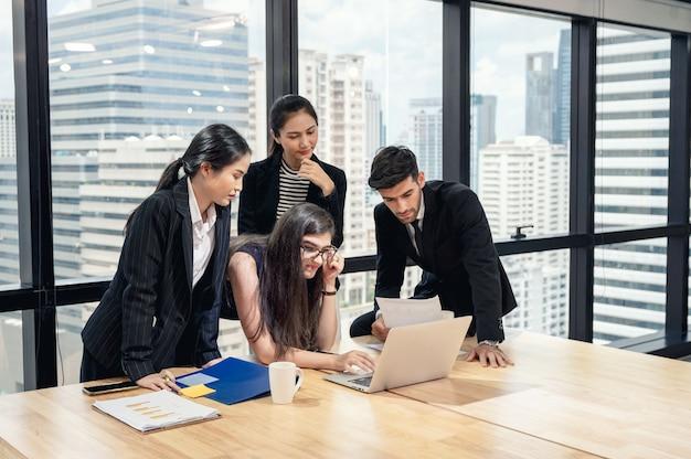 Wieloetniczny zespół biznesowy przeprowadza burzę mózgów i analizuje projekt biznesowy w nowoczesnym biurze w centrum miasta