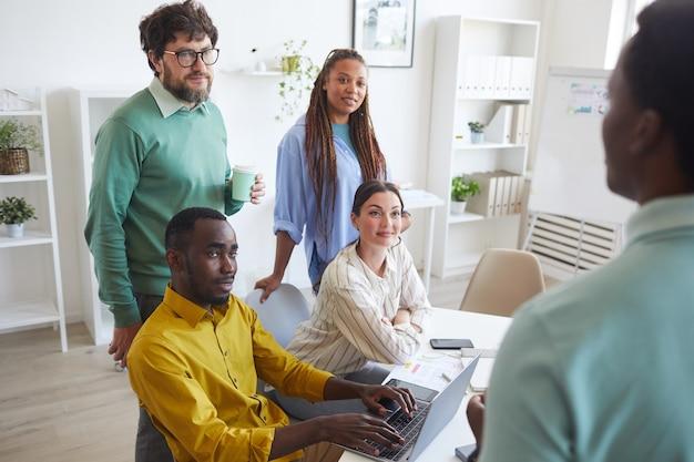 Wieloetniczny zespół biznesowy słuchający kolegi, dzieląc się pomysłami podczas spotkania w biurze