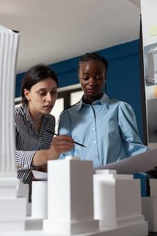 Wieloetniczny zespół roboczy patrzący na model budynku