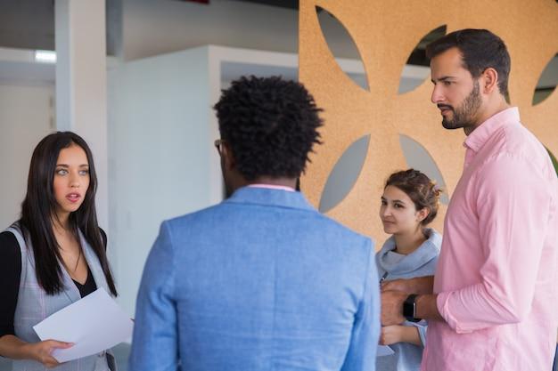 Wieloetniczny zespół startupowy omawiający problemy związane z pracą