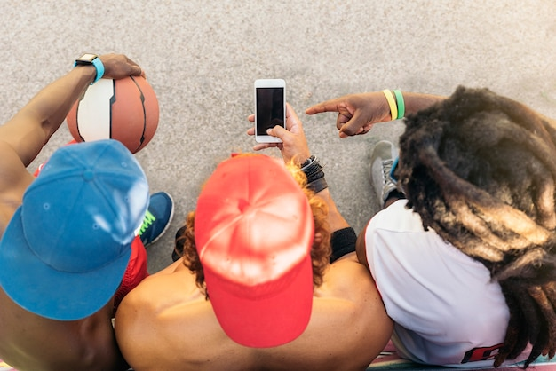 Wieloetnicznych znajomych korzystających z telefonu komórkowego podczas odpoczynku po grze w koszykówkę uliczną.