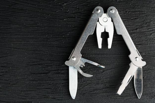 Wielofunkcyjne narzędzie na czarnym tle tekstury.