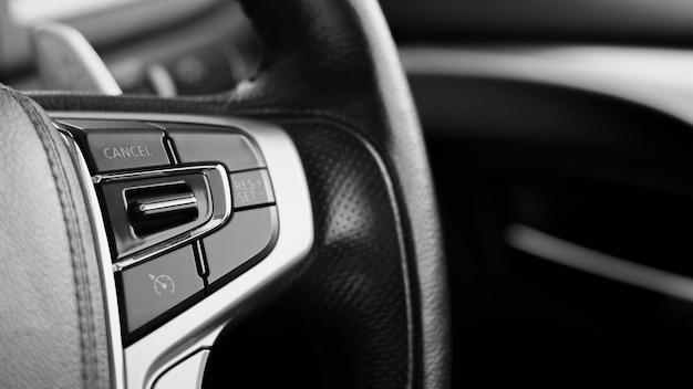 Wielofunkcyjne przyciski do szybkiej kontroli na czarnej kierownicy.