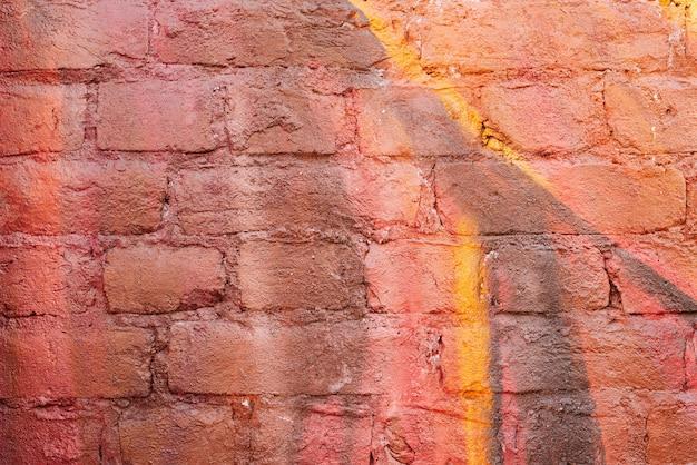 Wielokolorowa ceglana ściana w żywych burgundowych i żółtych kolorach.