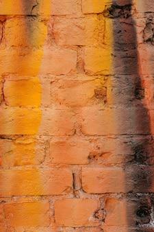Wielokolorowa ceglana ściana w żywych kolorach pomarańczu i żółci.