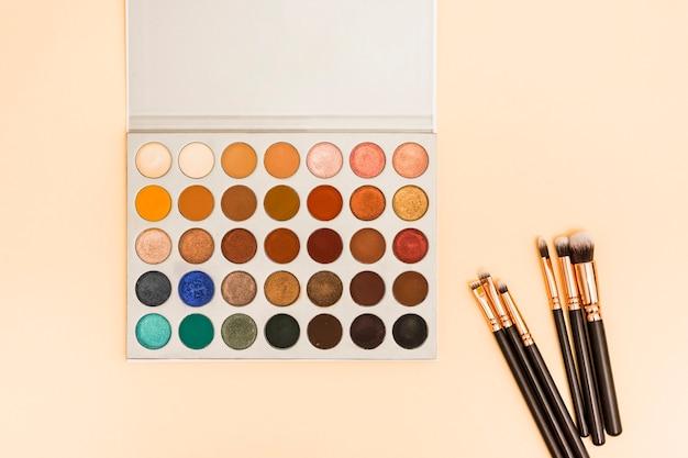 Wielokolorowa paleta cieni do powiek z pędzli do makijażu na kolorowym tle