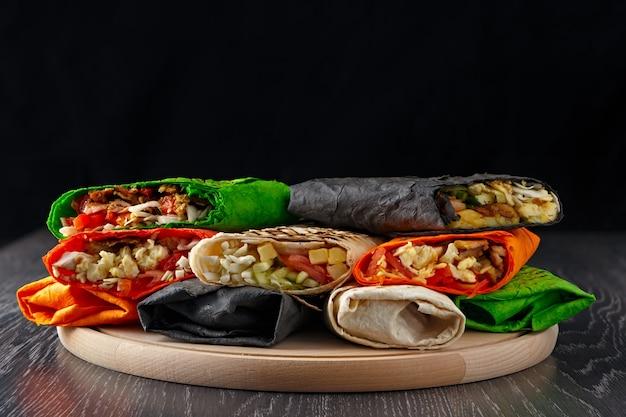 Wielokolorowa shawarma w chlebie pita jest krojona i leży na drewnianej powierzchni. danie bliskowschodnie przygotowywane jest na grillu i podawane z sosem.