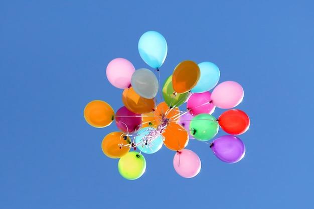 Wielokolorowe balony latające w błękitne niebo. dekoracje świąteczne