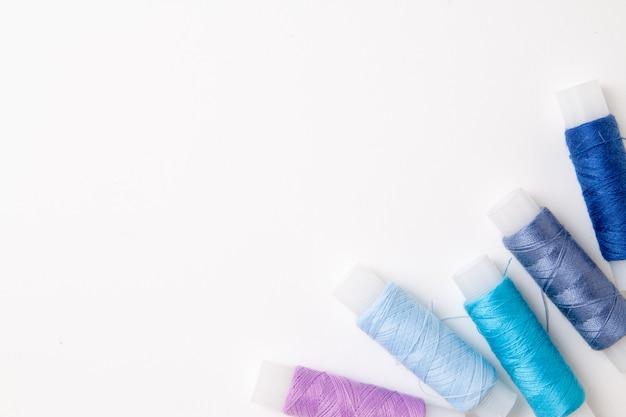 Wielokolorowe cewki nici na białym tle. materiały do szycia i akcesoria do robótek ręcznych