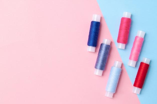 Wielokolorowe cewki nici na różowo niebieskim. copyspace. widok z góry