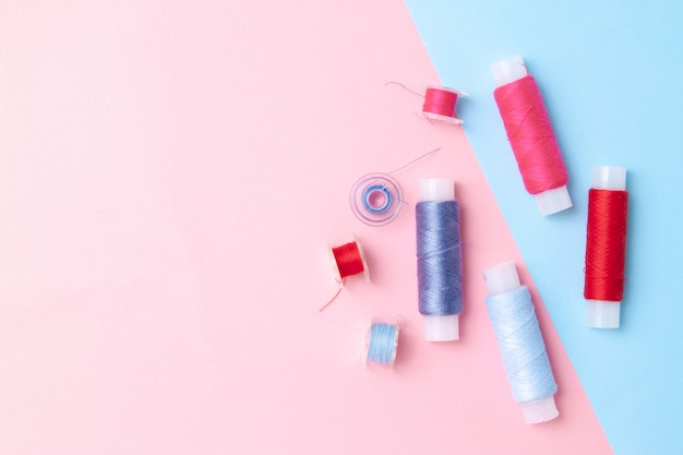 Wielokolorowe cewki nici na różowo niebieskim.