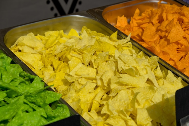 Wielokolorowe chipsy tortilla na tackach na gablocie. festiwal ulicznego jedzenia. selektywne skupienie.
