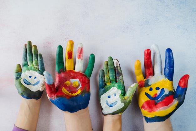 Wielokolorowe dłonie z pomalowanymi uśmiechniętymi twarzami