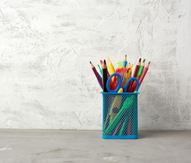 Wielokolorowe długopisy i ołówki oraz inne artykuły papiernicze w niebieskim metalowym uchwycie