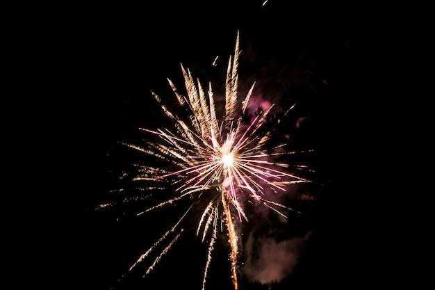 Wielokolorowe fajerwerki na tle ciemnego nieba. fajerwerki na cześć święta, nowy rok, boże narodzenie 2017. piękne duże fajerwerki na nocnym niebie