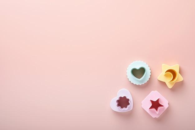 Wielokolorowe foremki do ciastek na różowym tle z miejscem na kopię reklamy i tekstu. koncepcja pieczenia. leżał płasko. makieta.