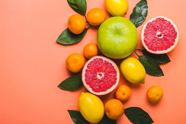 Wielokolorowe grejpfruty, cytryny i mandarynki. żywe koralowe tło. trend kolorystyczny 2019