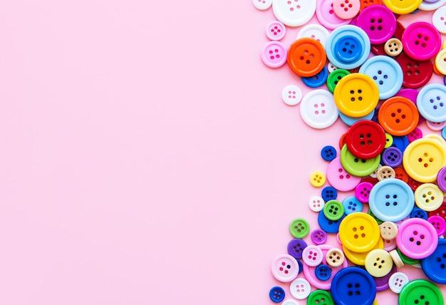 Wielokolorowe guziki do przyszywania na różowej pastelowej powierzchni. obramowanie do szycia, widok z góry