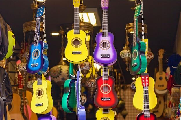 Wielokolorowe i jasne gitary wiszą w rzędzie w sklepie z instrumentami muzycznymi.