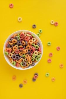 Wielokolorowe jasne suche śniadanie na żółtym tle