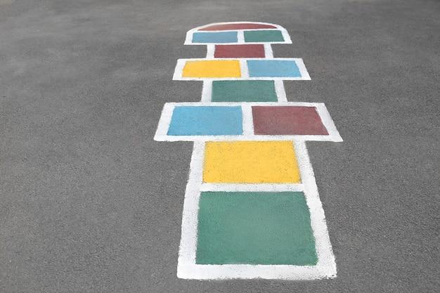 Wielokolorowe klasyki malowane na drodze. gra dla dzieci.