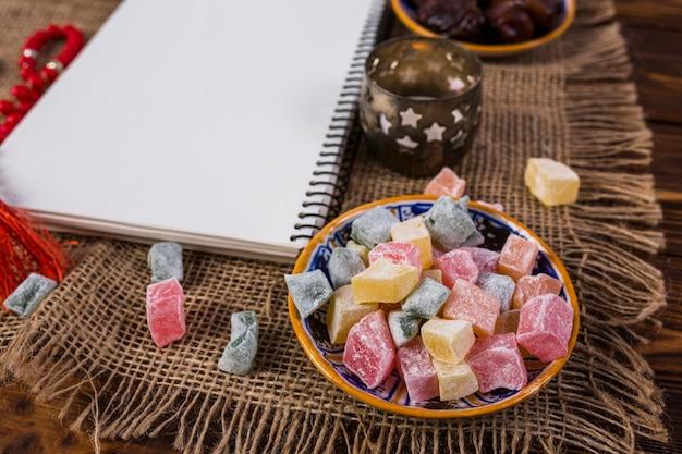 Wielokolorowe kostki rakhat-lukum w talerzu z pustym białym spiralnym notatnikiem i świecznikiem na obrusie workowym