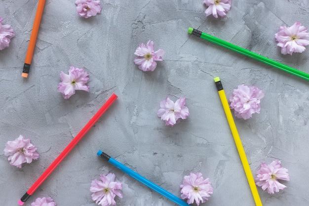 Wielokolorowe kredki i wiosenne lub letnie kwiaty