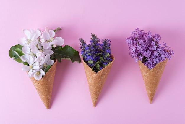 Wielokolorowe lody w kwiaty w minimalistycznej filiżance waflowej na różowym tle.