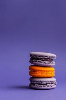 Wielokolorowe makaroniki na fioletowym tle. francuski deser na halloween. wypieki z mąki migdałowej.