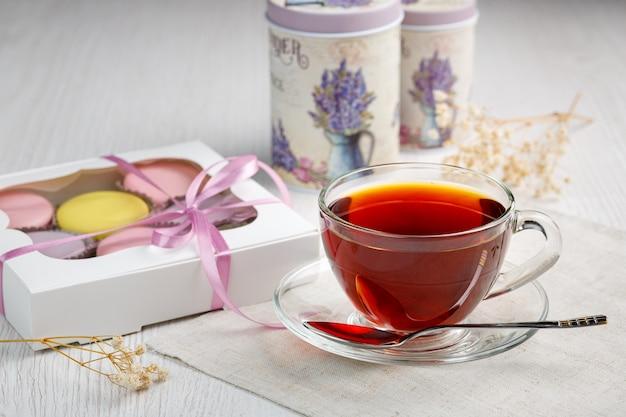 Wielokolorowe makaroniki w pudełku i filiżanka herbaty na stole kuchennym z jasnego drewna poranna herbata i słodycze