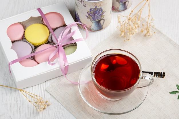 Wielokolorowe makaroniki w pudełku i filiżanka herbaty na stole kuchennym z jasnego drewna