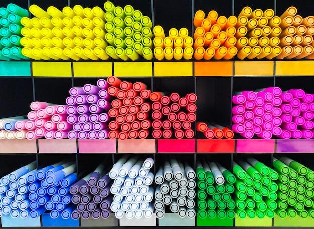 Wielokolorowe markery na półkach są ułożone w tęcze. artykuły papiernicze i narzędzia do kolorowania. koncepcja kreatywności - kolorowe długopisy do sztuki, warsztatu, rzemiosła. sklep z artykułami artystycznymi.