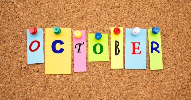 Wielokolorowe notatki z literami przypięte na tablicy ogłoszeń korka. miejsce do pracy.
