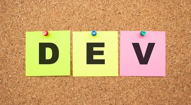 Wielokolorowe notatki z literami przypiętymi do tablicy korkowej word dev