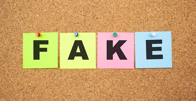 Wielokolorowe notatki z literami przypiętymi na tablicy korkowej. słowo fake. miejsce do pracy.