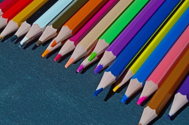 Wielokolorowe ołówki leżą na czarnym tle z teksturą.