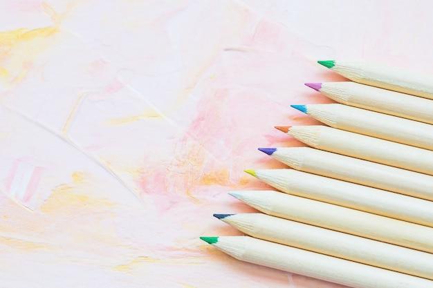 Wielokolorowe ołówki na różowym tle
