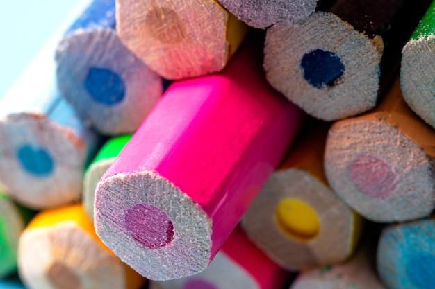 Wielokolorowe ołówki układane są na stole w formie piramidy, z bliska. motyw szkolny