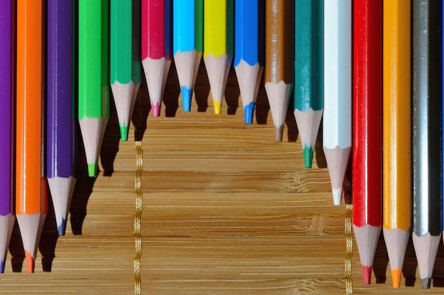 Wielokolorowe ołówki ułożone łukiem na słomianym tle.