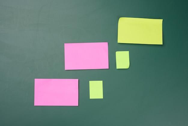 Wielokolorowe patyczki papierowe są przyklejone do zielonej tablicy, skopiuj miejsce