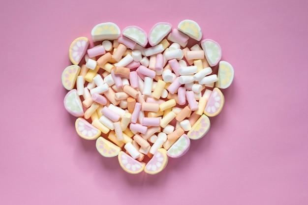 Wielokolorowe pianki w formie serca na różowym tle. widok z góry